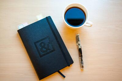 an AndPlus agenda, a pen and a cup of coffee
