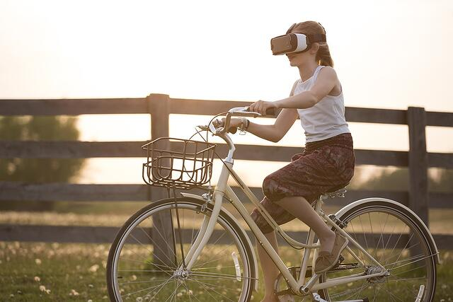 Woman riding bicycle while wearing virtual reality headset