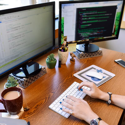 a person working in front of two monitors
