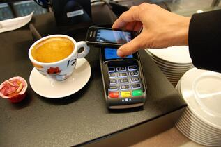 a buyer holding mobile phone over a payment scanner