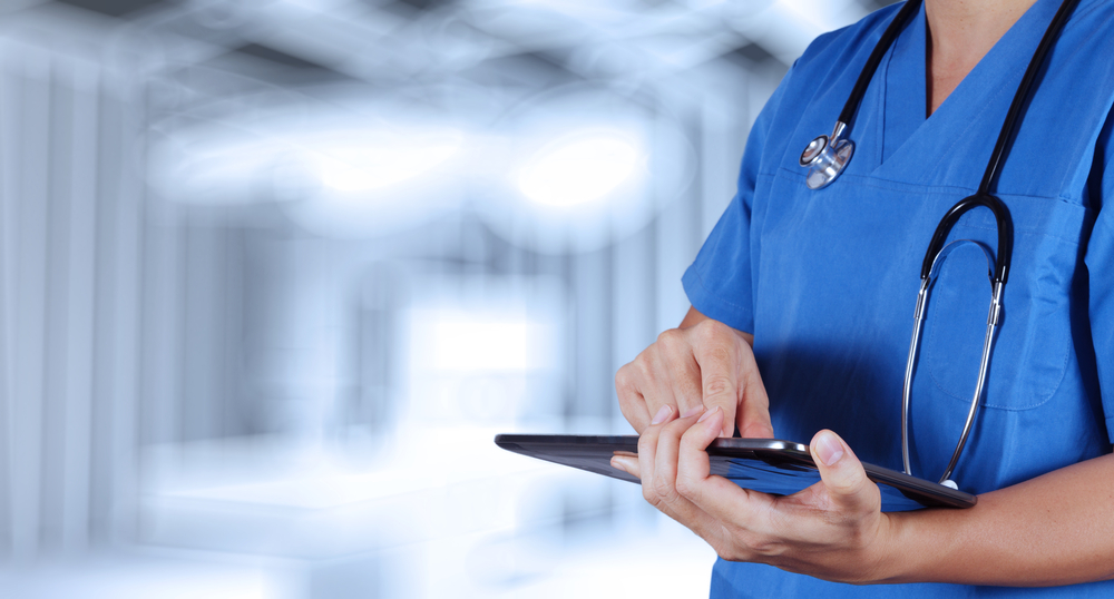 medical staff member operating tablet device